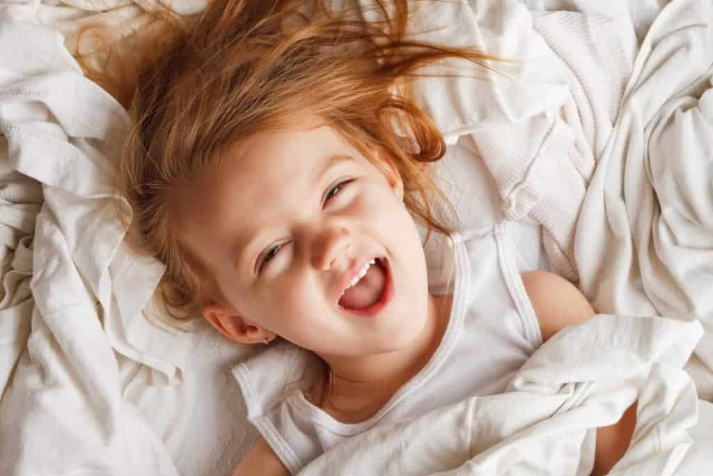 Is Your Child or Toddler Waking Up Too Early? How to Cope with Early Risers & Fix Sleep Problems. What could be causing your child wake up too early including the 18 month sleep regression and 20 month sleep regression. Solutions to stop kids waking up too early. What to do when your toddler wakes up too early and won't go back to sleep and tips for dealing with the 18 month sleep regression.