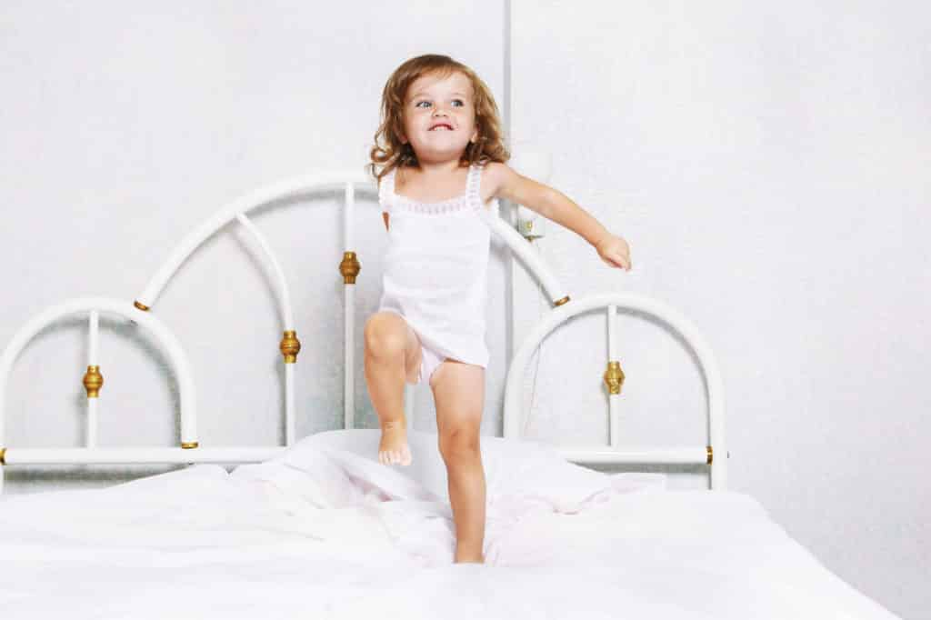 If your toddler is climbing out of the crib or you think they're ready to move to a big kid bed, it's best to read these words of caution and expert tips before you move them to a big bed. Making the transition to a big kid bed as easy as possible for everyone. Tips to transition to a big kid bed. Things to know before you move to a big kid bed. #bigkidbed #movetoabigkidbed #transitiontoabigkidbed #movingoutoftheircrib