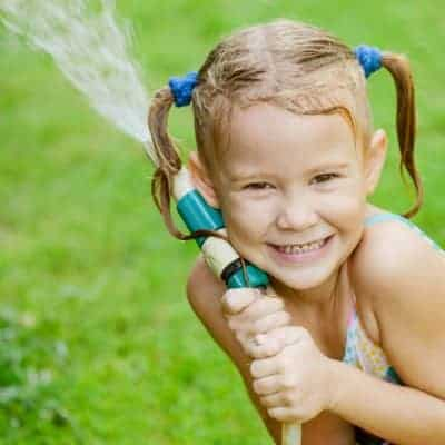 Ultimate Summer Bucket List and little girl playing in the water